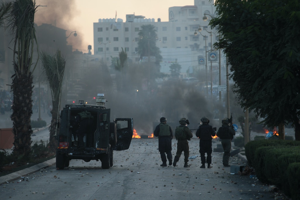 Israeli army stand next to their military vehicle, during clashes with Palestinian protesters on the north entrance of Ramallah city on Oct 16, 2015 in west bank.(Photo by Mohammad Alhaj/NurPhoto) *** Please Use Credit from Credit Field ***
