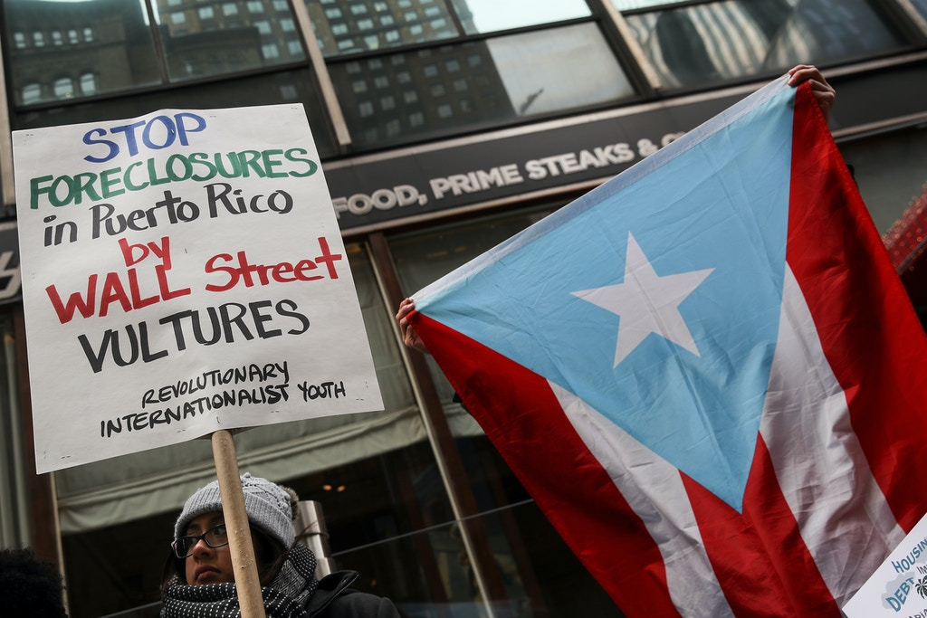 NEW YORK, NY - DECEMBER 20: Protestors rally against foreclosures on Puerto Rican families affected by Hurricane Maria, outside the offices of TPG Capital, December 20, 2017 in New York City. The activists claims that TPG Capital's mortgage service companies are aggressively foreclosing on families in Puerto Rico after many people were displaced from their homes following Hurricane Maria. (Photo by Drew Angerer/Getty Images)