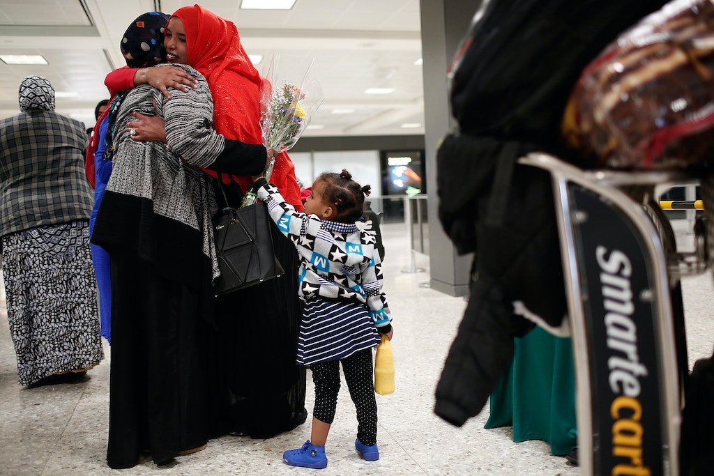 WASHINGTON, DC - FEBRUARY 06:  Three year old Mirhan Khafi (R) holds on to her mother Najma Abdishakur (C) as she hugs her mother Zahra Warsma (L) after arriving from Somalia at Dulles International airport on February 6, 2017 in Washington, DC. Abdishakur and her daughter were prohibited from entering the U.S. a week ago due to tightened immigration policies established by the Trump administration, but were able to travel freely this week following a court injunction halting the implementation of the immigration policy. (Photo by Win McNamee/Getty Images)