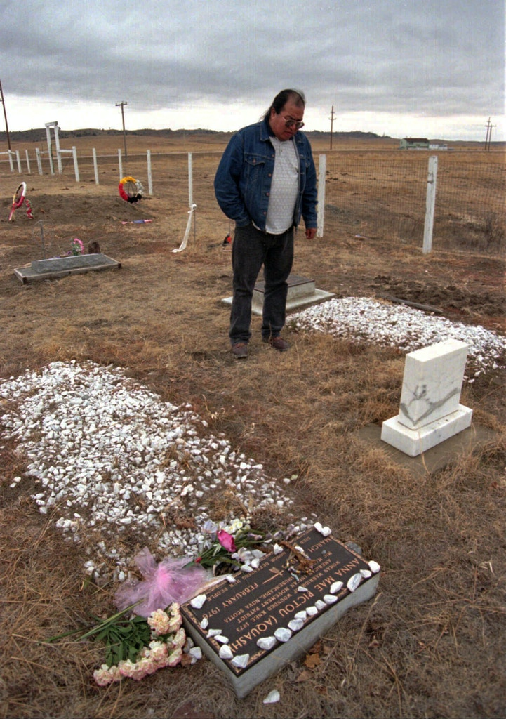 Edgar Bear Runner, co-coordinator of the 25th anniversary of Wounded Knee 1973, stands by the graves of Anna Mae Aquash and Joe Stuntz on Wednesday, Feb. 18, 1998, at the Little Family Cemetery in Oglala, S.D. Aquash and Stuntz were killed during the violence that followed the 71 day occupation of Wounded Knee in 1973.  The anniversary begins Friday Feb. 27 at the Pine Ridge Indian Reservation in South Dakota. (AP Photo/Jill Kokesh)