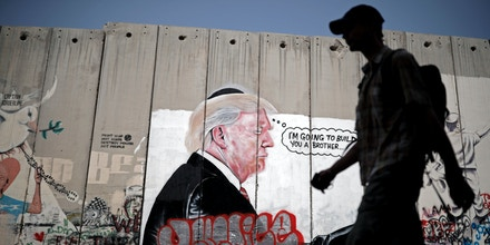 TOPSHOT - A man walks past graffiti depicting US President Donald Trump on the controversial Israeli separation barrier separating the West Bank town of Bethlehem from Jerusalem on August 25, 2017. / AFP PHOTO / THOMAS COEX        (Photo credit should read THOMAS COEX/AFP/Getty Images)