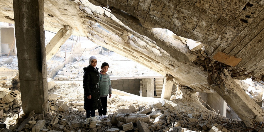 DAMASCUS, SYRIA - DECEMBER 14: 8-year-old Alaa and 10-year-old Noor, Syrian girls living in Syrias besieged Eastern Ghouta district under extremely difficult circumstances, are seen near the wreckage of a building at Eastern Ghouta on December 14, 2017 in Damascus, Syria. Two sisters, with the help of their mother, an English teacher, described the suffer and expectations of the children living in Damascus on their Twitter account named;