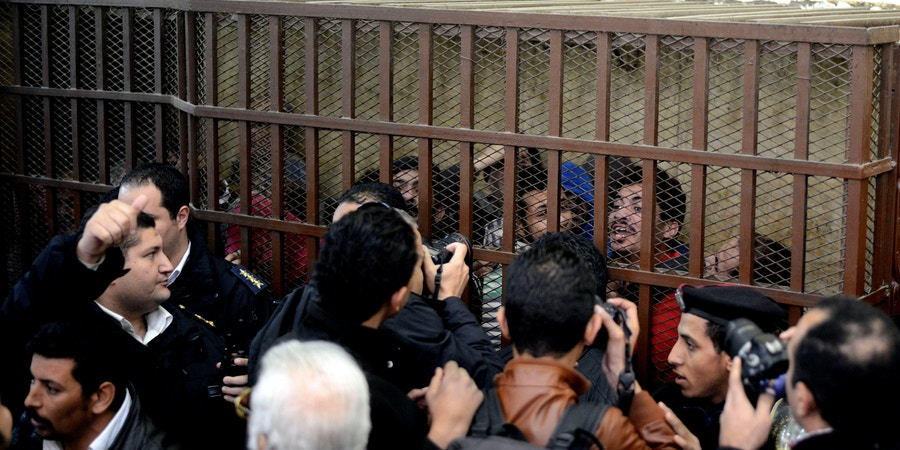Defendants react behind the bars at a court in Cairo following the acquittal on January 12, 2015 of 26 male men accused of