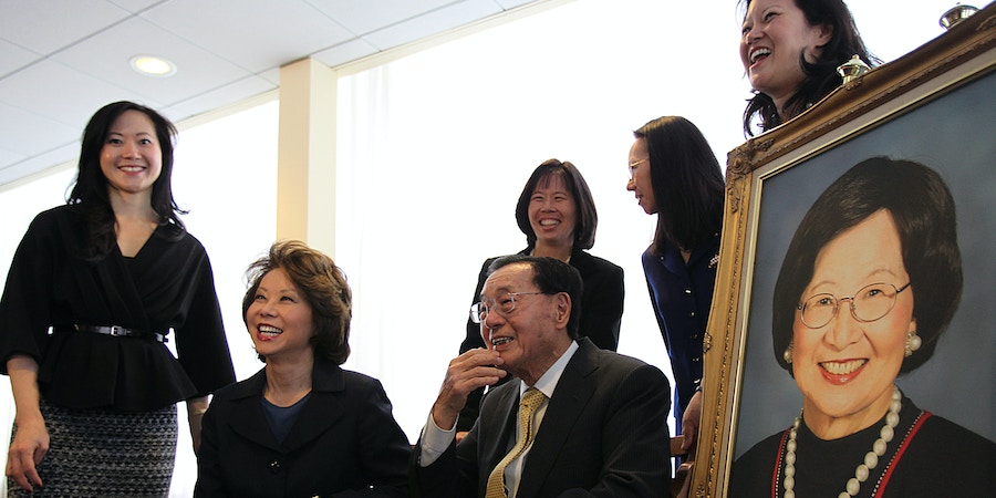 BOSTON - OCTOBER 12: Harvard University and Harvard Business School announced that they received a $40 million gift from a Doctor James S. C. Chao, and Family Foundation in tribute to the life and legacy of the late Ruth Mulan Chu Chao, the beloved matriarch of the prominent Chinese-American family. The Chao family is the only one in the history of the school to have had four daughters attend the Harvard Business School. A photo session after the press conference. The five remaining children of Dr. Chao and his late wife, Ruth Mulan Chu Chao, four of which attended Harvard Business School. Standing far left, is Angela. In back row is Christine who did not attend, May, and Grace. Sitting next to her father is the Honorable Elaine L. Chao, United States Secretary of Labor from 2001 to 2009 and the first Asian-American woman ever appointed to the President's cabinet in American History. Doctor James S. C. Chao is seated next to portrait of his late wife. (Photo by Suzanne Kreiter/The Boston Globe via Getty Images)