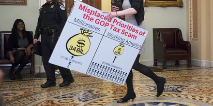 A Democratic aide carries a chart past the Senate chamber to be used by the minority to argue against the Republican tax bill, on Capitol Hill in Washington, Friday night, Dec. 1, 2017. (AP Photo/J. Scott Applewhite)