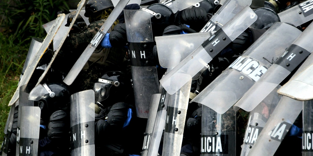Police officers in riot gear clash with supporters of Honduran presidential candidate for the Opposition Alliance against the Dictatorship coalition, Salvador Nasralla, near the Electoral Supreme Court (TSE), as the country waits for the final results of the week-end's presidential election, in Tegucigalpa, on November 30, 2017. Honduran President Juan Orlando Hernandez edged closer Thursday to winning a tense election as rival Nasralla said he will not recognize the result, claiming fraud. In a vote count dogged by computer failures and claims by Nasralla that the president was stealing the election, Hernandez had overturned a 5.0 percent deficit by early Thursday to lead by just 1.0 percent with 90 percent of the votes counted. / AFP PHOTO / Orlando SIERRA (Photo credit should read ORLANDO SIERRA/AFP/Getty Images)