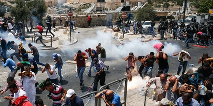 TOPSHOT - Palestinian worshippers run for cover from teargas fired by Israeli forces outside Jerusalem's Old City in front of the Al-Aqsa mosque compound, after Israeli police barred men under 50 from entering the Old City for Friday Muslim prayers as tensions rose and protests erupted over new security measures at the highly sensitive holy site on July 21, 2017. The ban came after Israeli ministers decided not to order the removal of metal detectors erected at entrances to the Al-Aqsa mosque compound, known to Jews as the Temple Mount, following an attack nearby a week ago that killed two policemen. / AFP PHOTO / AHMAD GHARABLI (Photo credit should read AHMAD GHARABLI/AFP/Getty Images)