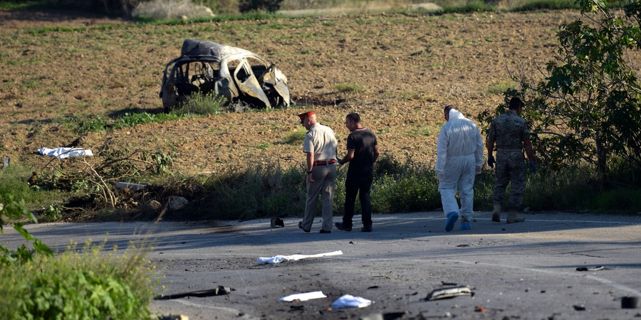 TOPSHOT - Police and forensic experts inspect the wreckage of a car bomb believed to have killed journalist and blogger Daphne Caruana Galizia close to her home in Bidnija, Malta, on October 16, 2017. The force of the blast broke her car into several pieces and catapulted the journalist's body into a nearby field, witnesses said. She leaves a husband and three sons.Caruana Galizia's death comes four months after Prime Minister Joseph Muscat's Labour Party won a resounding victory in a general election he called early as a result of scandals to which Caruana Galizia's allegations were central. / AFP PHOTO / STR / Malta OUT (Photo credit should read STR/AFP/Getty Images)
