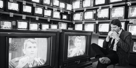 (Original Caption) 7/8/1987-Roseville, MI- Jim Marlowe, a sales consultant at Fretter Appliance in Roseville, MI, eats his lunch and watches Marine Lieutenant Oliver North testify before the House and Senate Iran-Contra hearing on a bank of televisions.