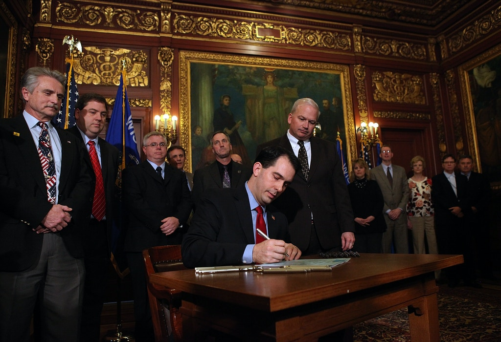 MADISON, WI - MARCH 11:  Republican Wisconsin State Legislatures look on as Wisconsin Gov. Scott Walker performs a ceremonial bill signing outside his office at the Wisconsin State Capitol on March 11, 2011 in Madison, Wisconsin. Gov. Walker signed his controversial budget repair bill into law on Friday as angry pro-union activists continued to demonstrate at the Wisconsin State Capitol.  (Photo by Justin Sullivan/Getty Images)