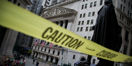 Caution tape hangs near the steps of Federal Hall across from the New York Stock Exchange (NYSE) in New York, U.S., on Monday, Nov. 20, 2017. The main U.S. equity gauge moved just a 10th of a percent last week, but investor hedging has jumped to a six-year high. Photographer: Michael Nagle/Bloomberg via Getty Images
