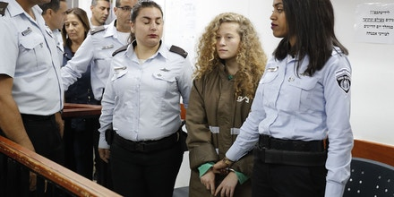 Palestinian Ahed Tamimi (C), 16-year-old prominent campaigner against Israel's occupation, appears at a military court at the Israeli-run Ofer prison in the West Bank village of Betunia on December 28, 2017. Ahed is only a teenager, but has repeatedly been at the centre of the seemingly endless propaganda war between Israelis and Palestinians, with a video of her slapping soldiers the latest example. / AFP PHOTO / Ahmad GHARABLI (Photo credit should read AHMAD GHARABLI/AFP/Getty Images)