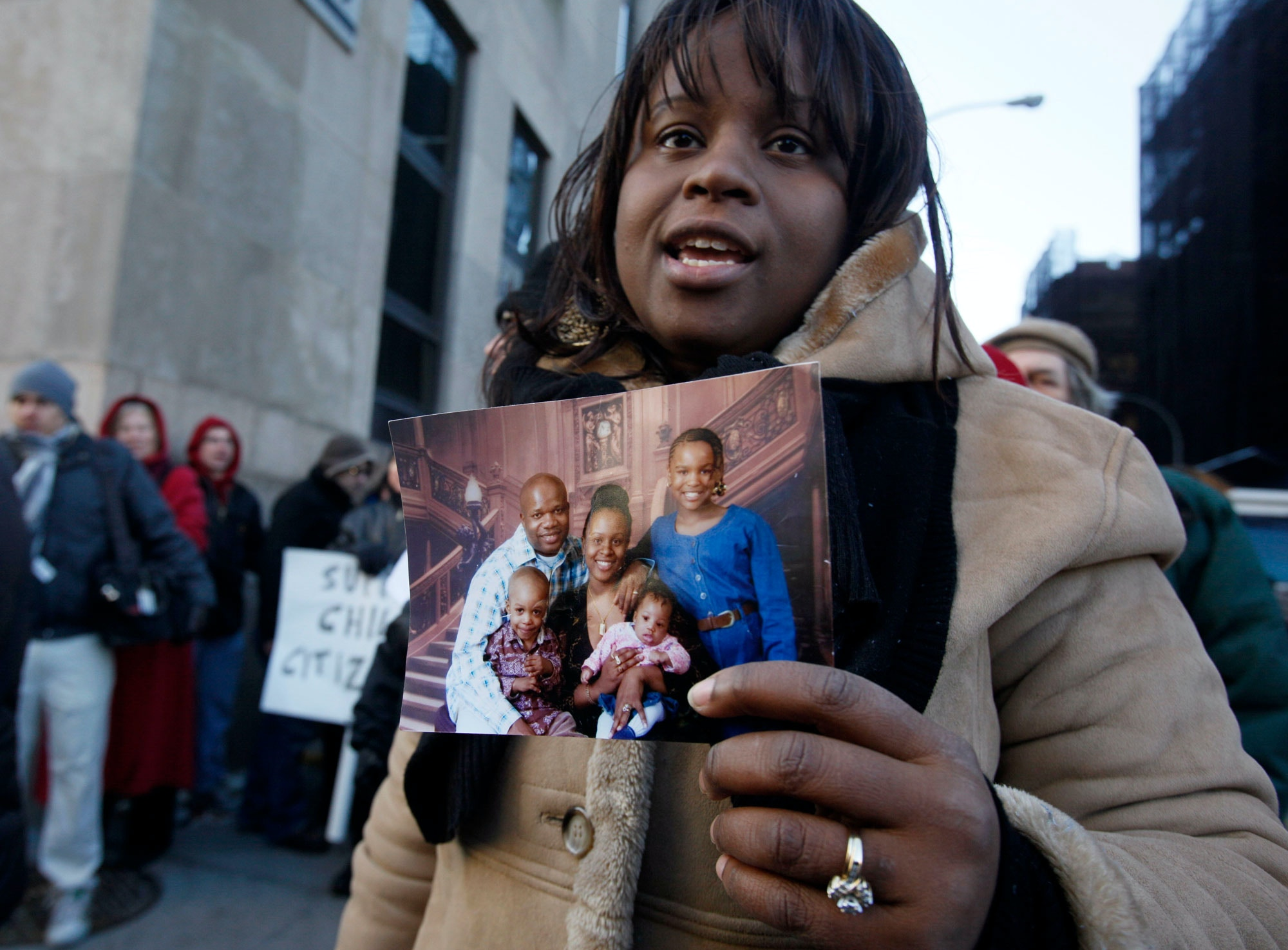 Jani Montrevil, wife of Jean Montrevil holds a photo of her family during a demonstration to protest the incarceration and possible deportation of her husband Jean Montrevil,Tuesday, Jan. 5, 2010 in New York. She was protesting the detention of her husband facing deportation decades after his drug conviction. The New Sanctuary Coalition of New York City said Montrevil has been detained by Immigration and Customs Enforcement officials since Dec. 30. In the photo are Jean Montrevil, left, holding son Jahsiah, Jani, center holding daughter Jamya, and daughter Janiah. (AP Photo/Mary Altaffer)