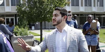 In this Tuesday, Aug. 8, 2017 photo, Dr. Abdul El-Sayed talks with Jermaine Jones in Detroit. Perhaps no state has embraced the political outsider as much as Michigan. But El-Sayed, a 32-year-old liberal doctor, is putting that affinity for newcomers to the test by mounting a surprisingly strong bid to become the nation's first Muslim governor. (AP Photo/Carlos Osorio)