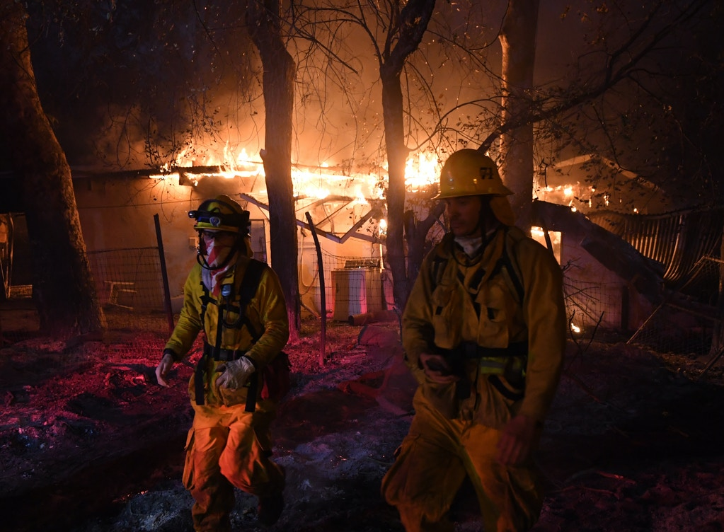 TOPSHOT - Firefighters move away from a burning house after discovering downed live power lines, as the Thomas wildfire continues to burn in Carpinteria, California, on December 10, 2017.The Thomas fire is only 15 percent contained, now threatening the city of Santa Barbara and the nearby coastal town of Carpinteria, making it one of the worst wildfires in California history. / AFP PHOTO / MARK RALSTON (Photo credit should read MARK RALSTON/AFP/Getty Images)