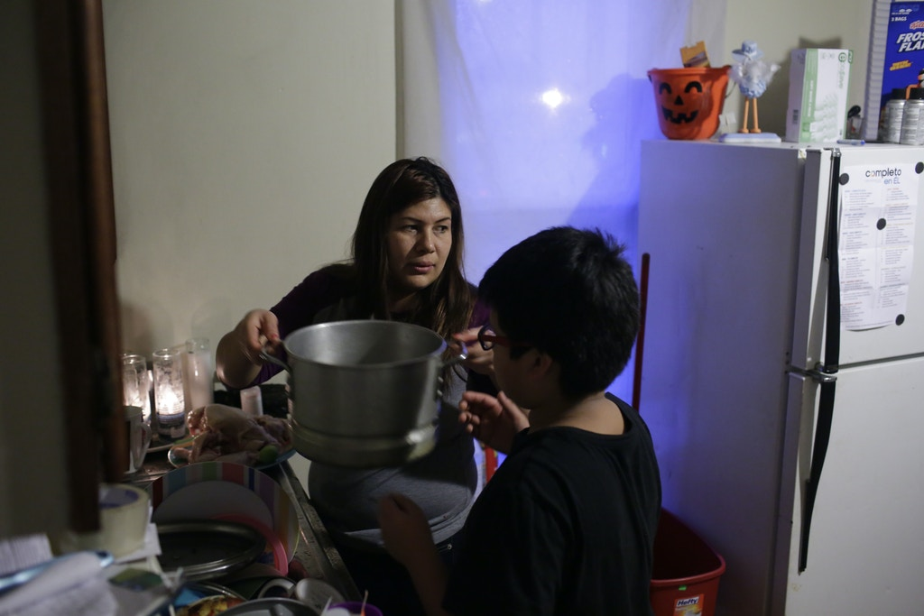 Celene Adame receives help from one of her sons as she prepared dinner at her home Thursday, January 11, 2018 in Chicago, Illinois. Adame's husband Wilmer Catalan-Ramirez was arrested by U.S. Immigration and Customs Enforcement after they showed up at his home last year in March. Catalan-Ramirez  has been separated from his family and detained since his arrest. Photo by Joshua Lott for The Intercept