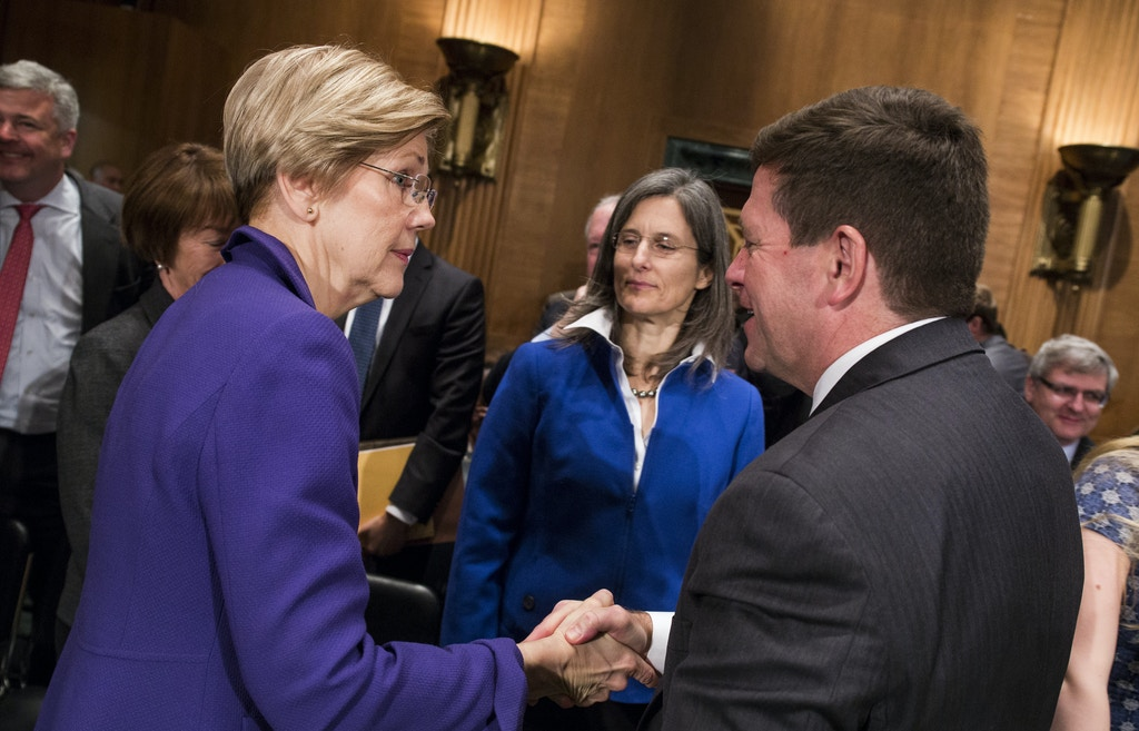 Jay Clayton, chairman of U.S. Securities and Exchange Commission (SEC) nominee for President Donald Trump, right, shakes hands with Senator Elizabeth Warren, a Democrat from Massachusetts, after testifying during a Senate Banking Committee confirmation hearing in Washington, D.C., U.S., on Thursday, March 23, 2017. Trump tapped Clayton to lead the SEC in January, saying the Sullivan & Cromwell partner would ensure that financial companies thrive and create jobs, while still playing by the rules. Photographer: Zach Gibson/Bloomberg via Getty Images