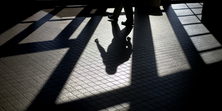 In this Friday, Dec. 7, 2012 photo, the shadow of a Georgia Department of Juvenile Justice correctional officer is cast as he leaves a training facility following a graduation from the Sergeants Academy, in Forsyth, Ga. Internal investigations have found that proper procedures were routinely ignored at some Georgia juvenile detention facilities, and the recently departed commissioner launched a series of investigations that led to numerous firings and suspensions for employee misconduct. While constant turnover in top leadership has inevitably caused some instability, that's not the root of the department's problems, say current and former leaders in the department, as well as outside observers. More problematic, they say, are budget cuts that, among other things, make it hard to attract and train employees qualified to deal with young offenders who often have violent tendencies. (AP Photo/David Goldman)