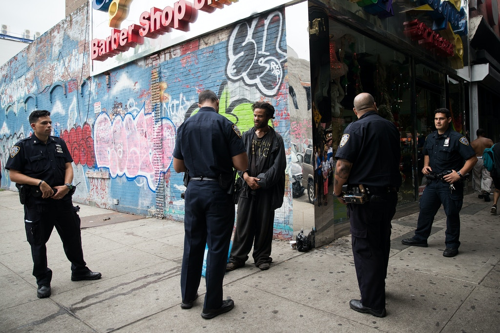 NEW YORK, NY - JULY 14: New York City police officers stop a man for suspected K2 possession, July 14, 2016 on the border of the Bedford-Stuyvesant and Bushwick neighborhoods in the Brooklyn borough of New York City. The man handed over an empty K2 packet to police. Following a wave of suspected K2 overdoes on Tuesday, New York City police raided five convenience stores on Wednesday. (Photo by Drew Angerer/Getty Images)