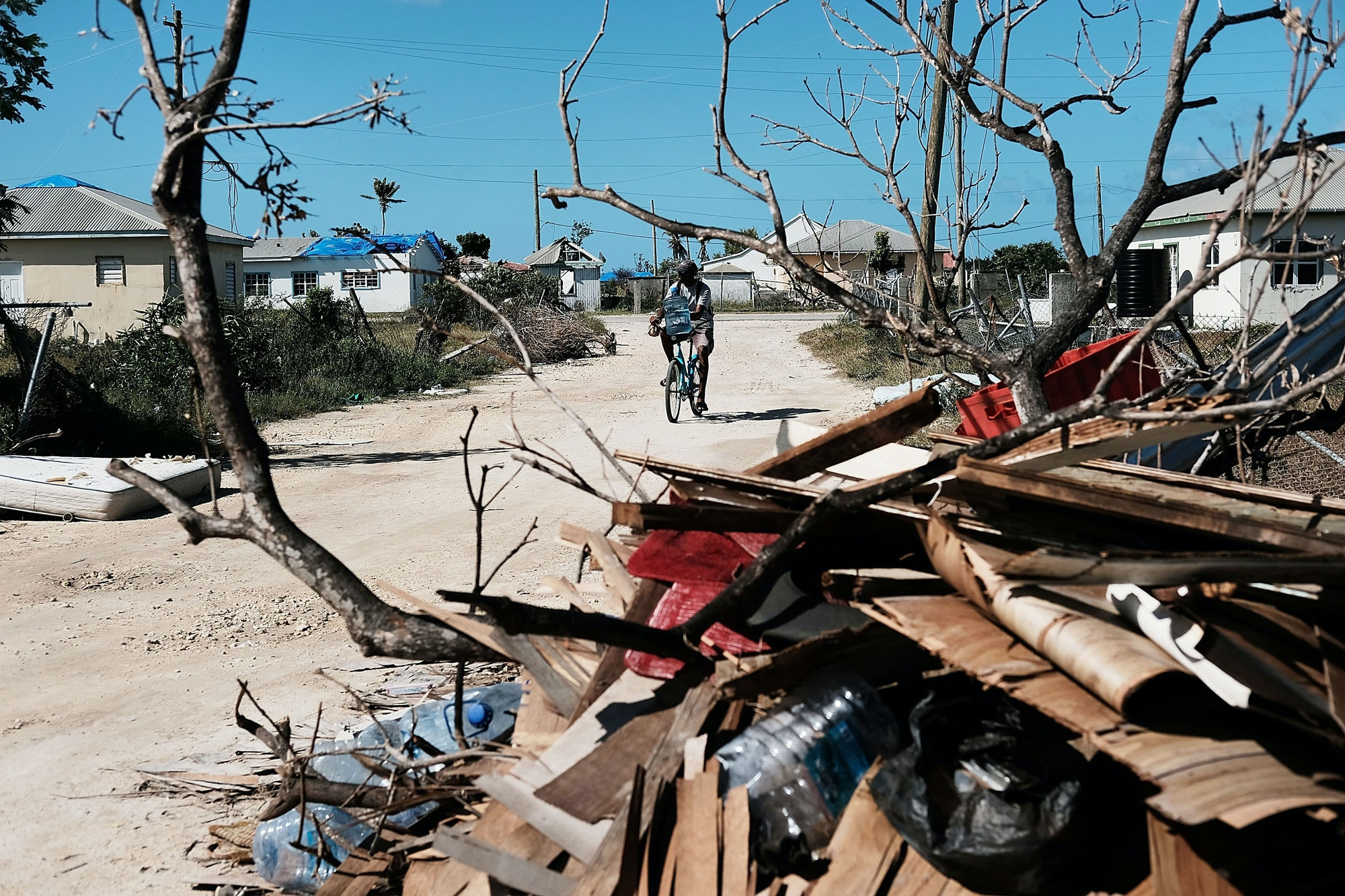 CODRINGTON, BARBUDA - DECEMBER 08: Debris from damaged homes lines a street on the nearly destroyed island of Barbuda on December 8, 2017 in Cordington, Barbuda. Barbuda, which covers only 62 square miles, was nearly leveled when Hurricane Irma made landfall with 185mph winds on the night of  September six. Only two days later, fearing Barbuda would be hit again by Hurricane Jose, the prime minister ordered an evacuation of all 1,800 residents of the island. Most are now still in shelters scattered  around Barbuda's much larger sister island Antigua.  (Photo by Spencer Platt/Getty Images)