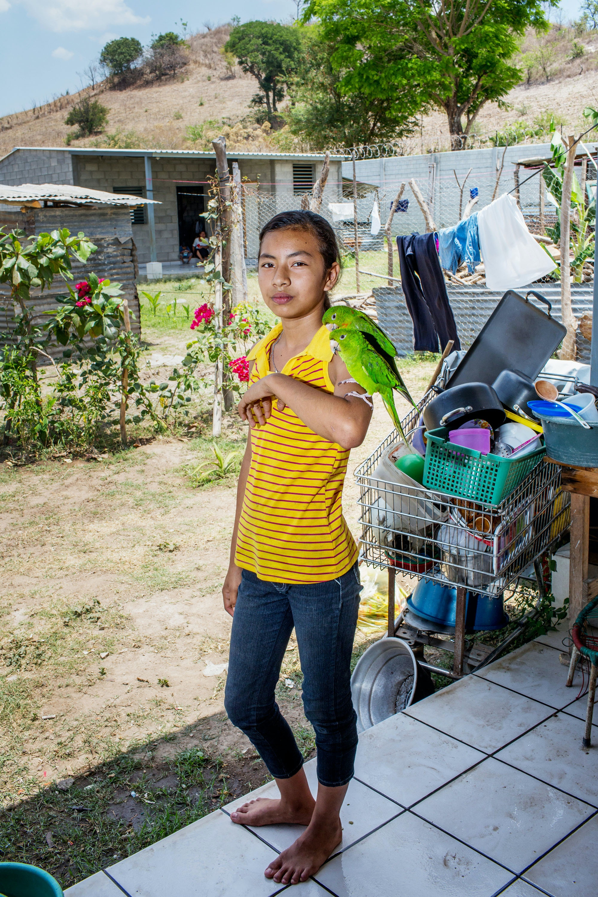 April 2017, El Salvador, San Salvador. 13 year old Kenya Fabiola Gonzales Trinidad holds her pet parrots on her arm at her home outside of San Salvador. She has just moved to the new community of new cinder block 3 room houses built with church donations, because her old neighborhood where she lived with her brother and grandfather was too dangerous due to gang activity. (Natalie Keyssar)