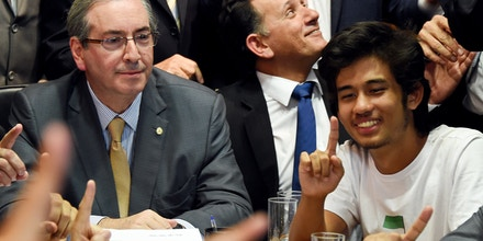 Kim Kataguiri (R), leader of the Free Brazil Movement (MBL), meets with Brazilian Lower House President Eduardo Cunha in Brasilia, Brazil on May 27, 2015. Kataguiri, a 19-year-old college drop out, is the face of MBL, a growing force which seeks to harness some of the energy of the 2013 protest movement which brought more than a million onto the streets. AFP PHOTO/EVARISTO SA        (Photo credit should read EVARISTO SA/AFP/Getty Images)