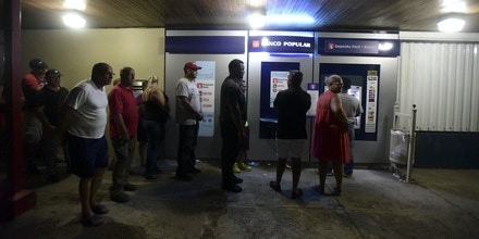 Clients of Popular Bank of Puerto Rico wait in line at the Carolina Shopping Court branch to withdraw cash from their accounts after the passage of Hurricane Maria, in Carolina, Puerto Rico, Wednesday, September 27, 2017. Because of the communications blackout caused by Maria, cash is the only way to buy gasoline and basic supplies. (AP Photo/Carlos Giusti)