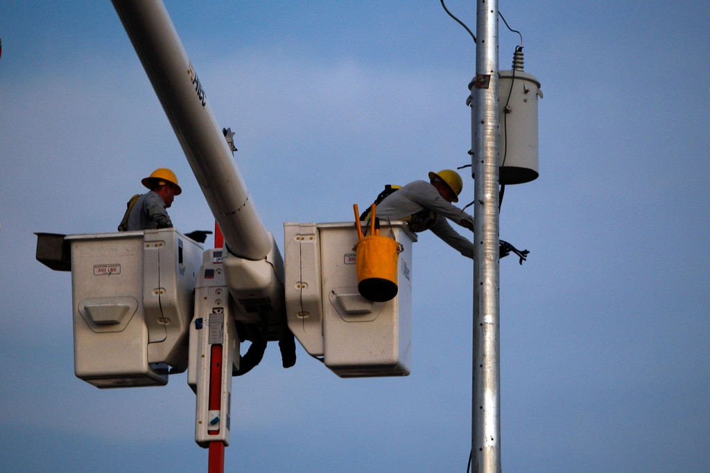 A Puerto Rico Electric and Power Authority lineman attaches an electrical insulator to a new utility pole in a residential area in Gurabo, Puerto Rico on November 29, 2017. / AFP PHOTO / Ricardo ARDUENGO / TO GO WITH AFP STORY By Leila MACOR, US-PuertoRico-power-weather-reconstruction-hurricane        (Photo credit should read RICARDO ARDUENGO/AFP/Getty Images)