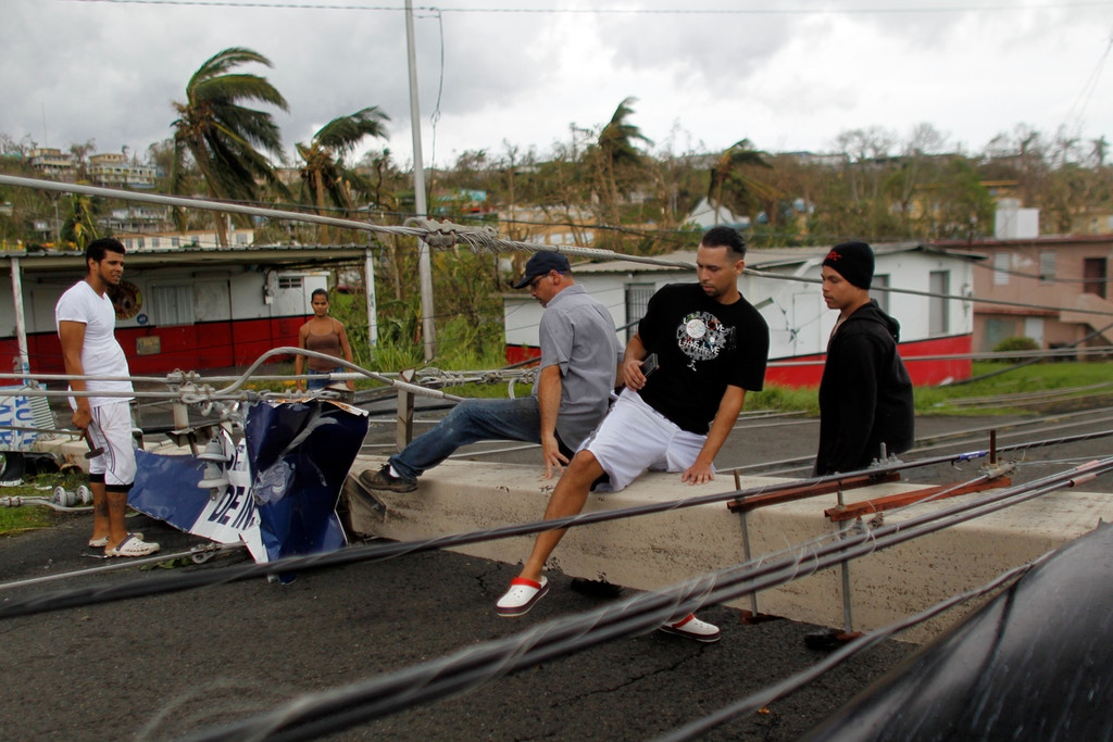 "People pass over a downed power line concrete post in the aftermath of Hurricane Maria in Luquillo, Puerto Rico, Thursday, September 21, 2017.Puerto Rico braced for potentially calamitous flash flooding after being pummeled by Hurricane Maria which devastated the island and knocked out the entire electricity grid. The hurricane, which Puerto Rico Governor Ricardo Rossello called ""the most devastating storm in a century,"" had battered the island of 3.4 million people after roaring ashore early Wednesday with deadly winds and heavy rain. / AFP PHOTO / Ricardo ARDUENGO (Photo credit should read RICARDO ARDUENGO/AFP/Getty Images)"