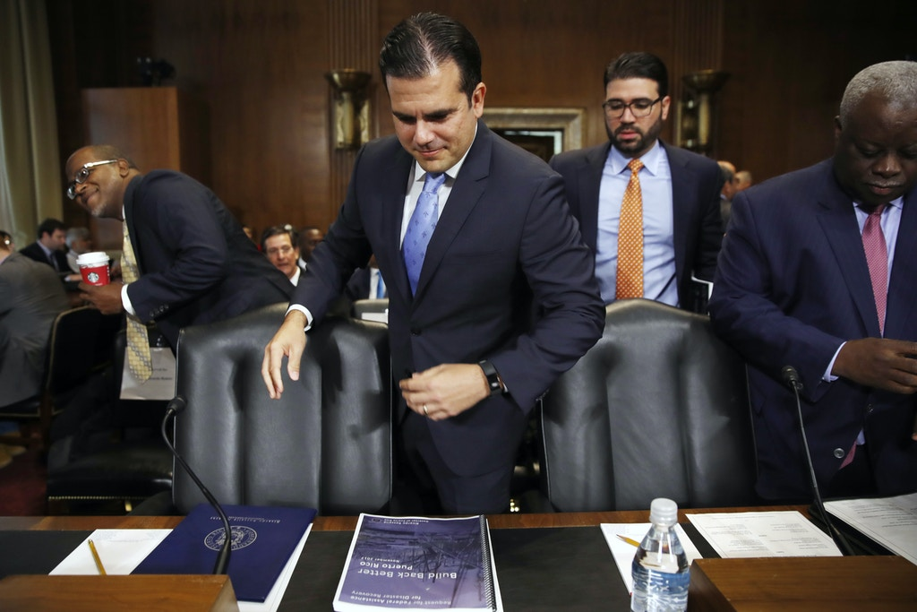 Puerto Rico Gov. Ricardo Rossello, center, takes his seat next to U.S. Virgin Islands Gov. Kenneth Mapp, right, as they arrive for a Senate Committee on Energy and Natural Resources hearing on hurricane recovery, Tuesday, Nov. 14, 2017, on Capitol Hill in Washington. (AP Photo/Jacquelyn Martin)