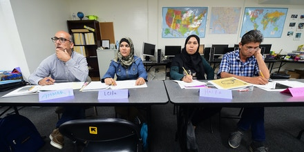 Syrian refugees listen to their Vocational ESL instructor Mary Cory at the International Rescue Committee center in San Diego on August 31, 2016. Seated from left to right are: Ammar Kawkab, Leila Murjan, Haifa Suliman and Abed Bar Mallah Haji. The United States has taken in10,000 Syrian refugees in 2016 as part of a resettlement program that has emerged as a hot-button issue in the US presidential campaign. / AFP / Frederic J. BROWN (Photo credit should read FREDERIC J. BROWN/AFP/Getty Images)