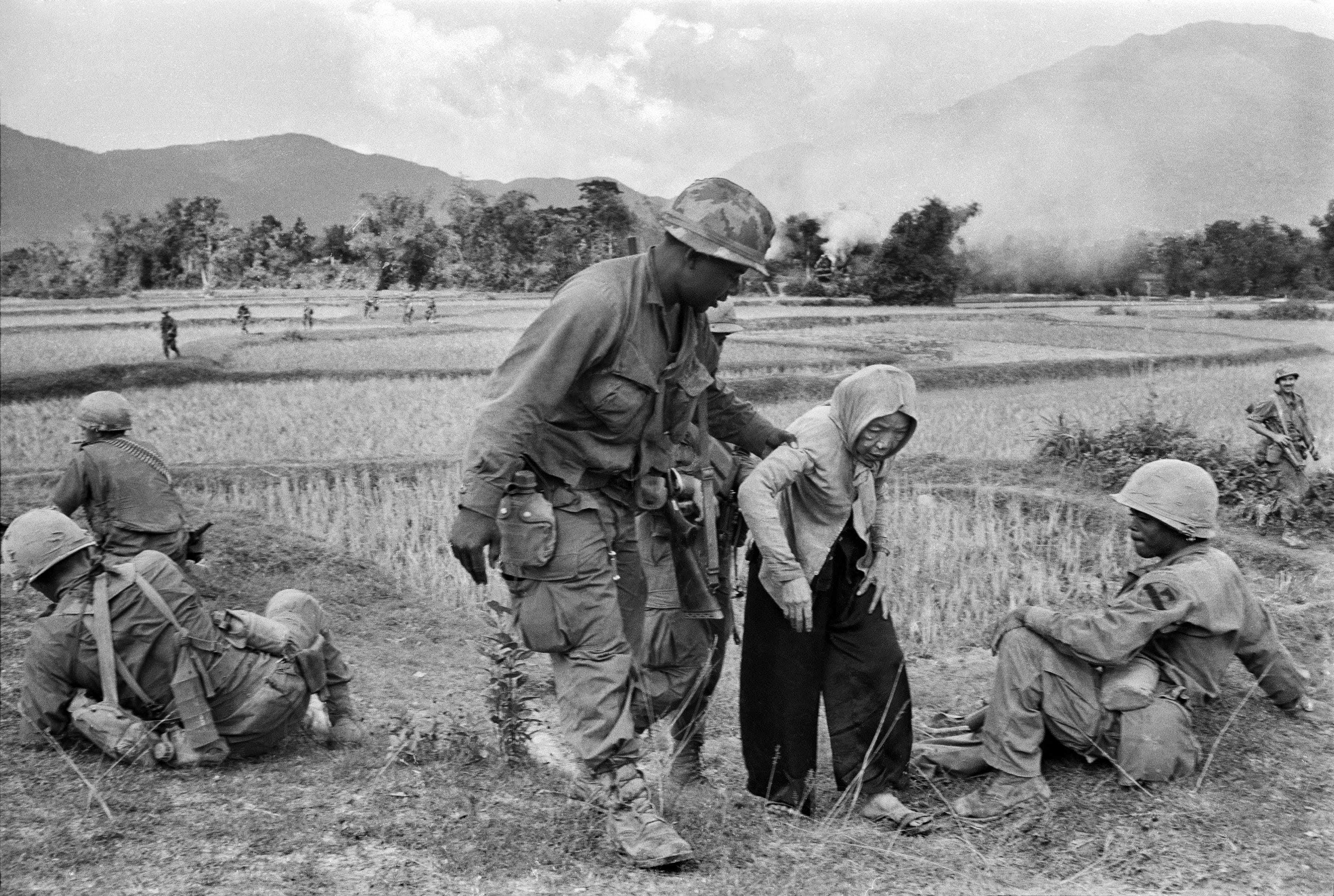 A U.S. air cavalryman lends a helping hand to an aged Vietnamese woman who grew tired as she and her neighbors were being resettled from their village to a refugee camp, Jan. 5, 1968. Other villagers had refused to assist her because, according to custom, they would then have borne responsibility for her for the remainder of her life. (AP Photo/Dang Van Phuoc)