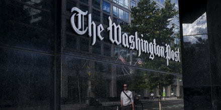 A man walks past The Washington Post on August 5, 2013 in Washington, DC after it was announced that Amazon.com founder and CEO Jeff Bezos had agreed to purchase the Post for USD 250 million.  Multi-billionaire Bezos, who created Amazon, which has soared in a few years to a dominant position in online retailing, said he was buying the Post in his personal capacity and hoped to shepherd it through the evolution away from traditional newsprint.   AFP PHOTO/Brendan SMIALOWSKI        (Photo credit should read BRENDAN SMIALOWSKI/AFP/Getty Images)