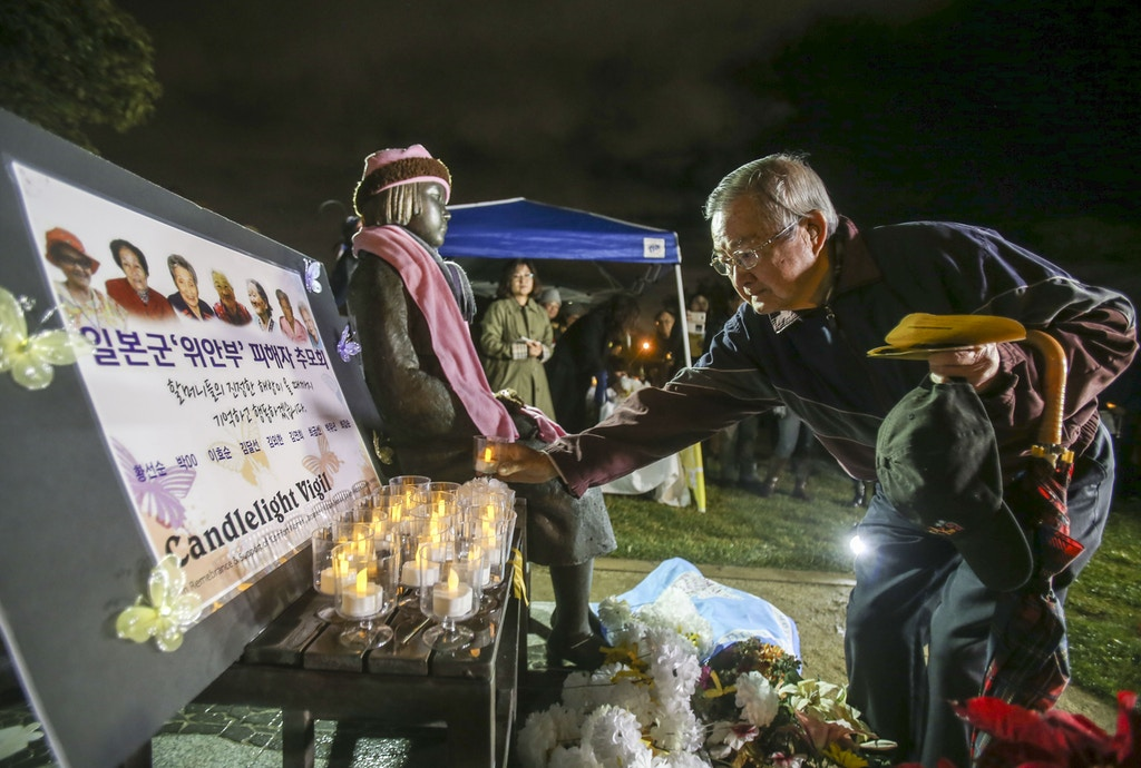 "A supporter offers flowers to a memorial statue honoring ""Comfort Women"" at Glendale Peace Monument  during a candlelight vigil in remembrance and support of ""Comfort Women"", Japanese military sexual slavery victims during World War II, on January 5, 2016, in Glendale, California. AFP PHOTO / Ringo Chiu / AFP / RINGO CHIU        (Photo credit should read RINGO CHIU/AFP/Getty Images)"