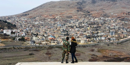 A Syrian military spokesperson (L) points to the Israeli-occupied Golan Heights on Dec. 23, 2017, in Al Gunaytirah in southwestern Syria.
