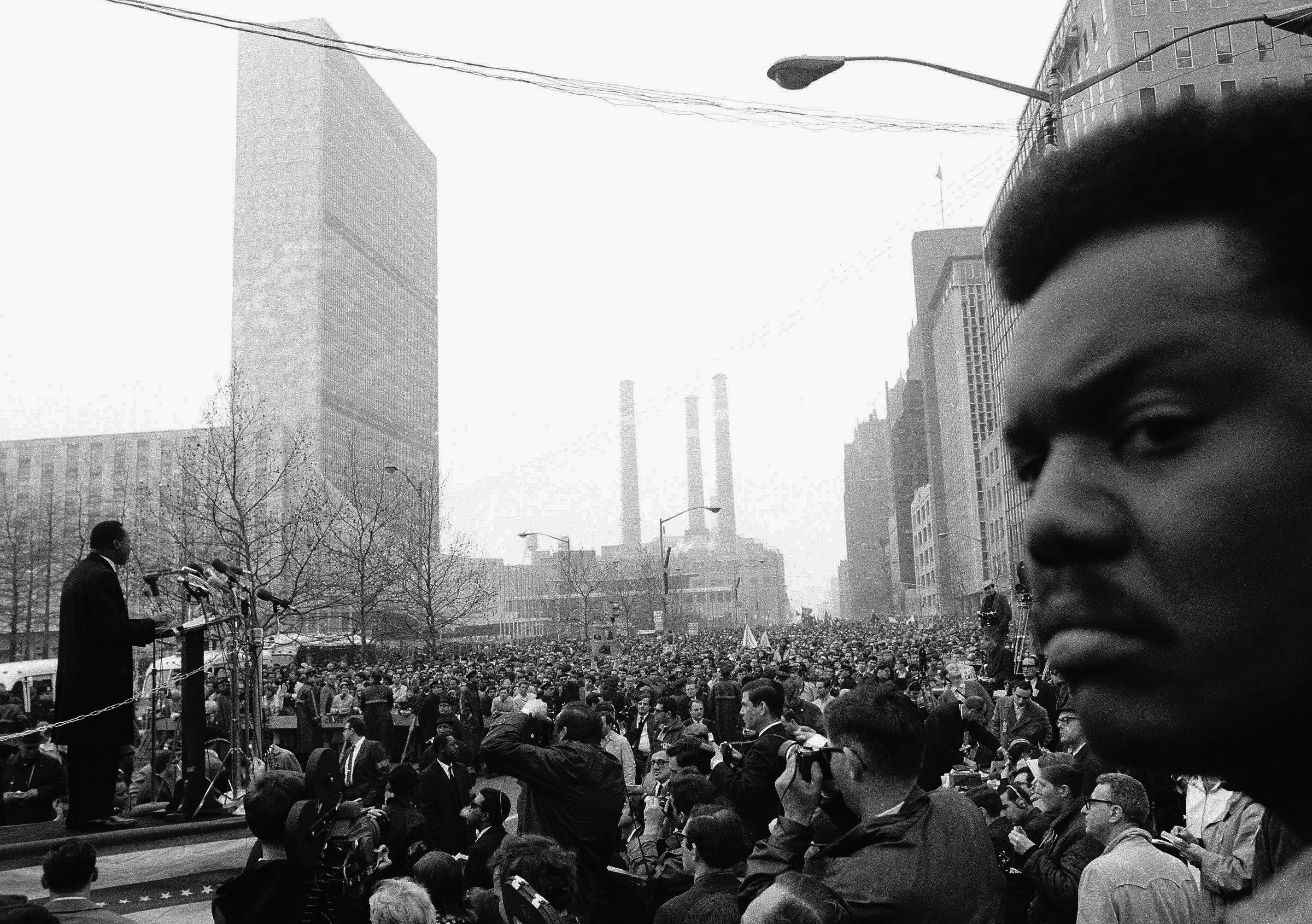 """Dr. Martin Luther King on platform talks to thousands of demonstrators on United Nations Plaza on April 15. 1967 in New York City.     The demonstrators were protesting  the war in Vietnam.   Dr. King was one of the Leaders of the March called the """"Spring Mobilization against the war in Vietnam"""". (AP Photo)"""