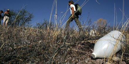 PIMA COUNTY, ARIZONA - JUNE 16:  Volunteers on patrol with the humanitarian group No More Deaths pass a discarded water jug on a trail used by migrants illegally entering the U.S. from Mexico June 16, 2006 in Pima County, Arizona. Since 1998 over 2,650 men, women and children have died attempting to cross the U.S.-Mexico border. According to the U.S. Border Patrol, a record 473 illegal immigrants died while trying to cross the U.S.-Mexico border during the fiscal year that ended September 30, 2005. No More Deaths runs 24-hour camps in the desert conducting search and rescue patrols for migrants in distress.  (Photo by Spencer Platt/Getty Images)