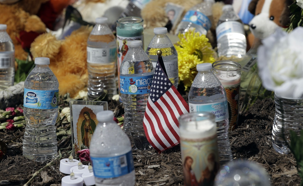 A U.S. flag, flowers, candles, and bottles of water help create a make-shift memorial in the parking lot of a Walmart store near the site where authorities Sunday discovered a tractor-trailer packed with immigrants outside a Walmart, Wednesday, July 26, 2017, in San Antonio. Several people died and others hospitalized after being crammed into a sweltering tractor-trailer in the midsummer Texas heat in what authorities describe as an immigrant-smuggling attempt gone wrong. (AP Photo/Eric Gay)