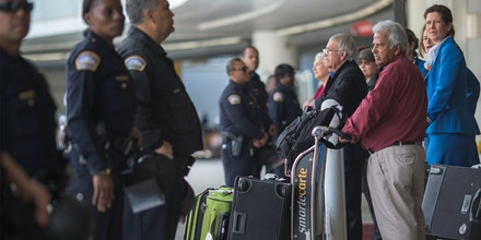 Arriving international travelers cross a police line separating pro- and anti-demonstrators of a ruling by a federal judge in Seattle that grants a nationwide temporary restraining order against the presidential order to ban travel to the United States from seven Muslim-majority countries, at Tom Bradley International Terminal at Los Angeles International Airport on February 4, 2017 in Los Angeles, California.