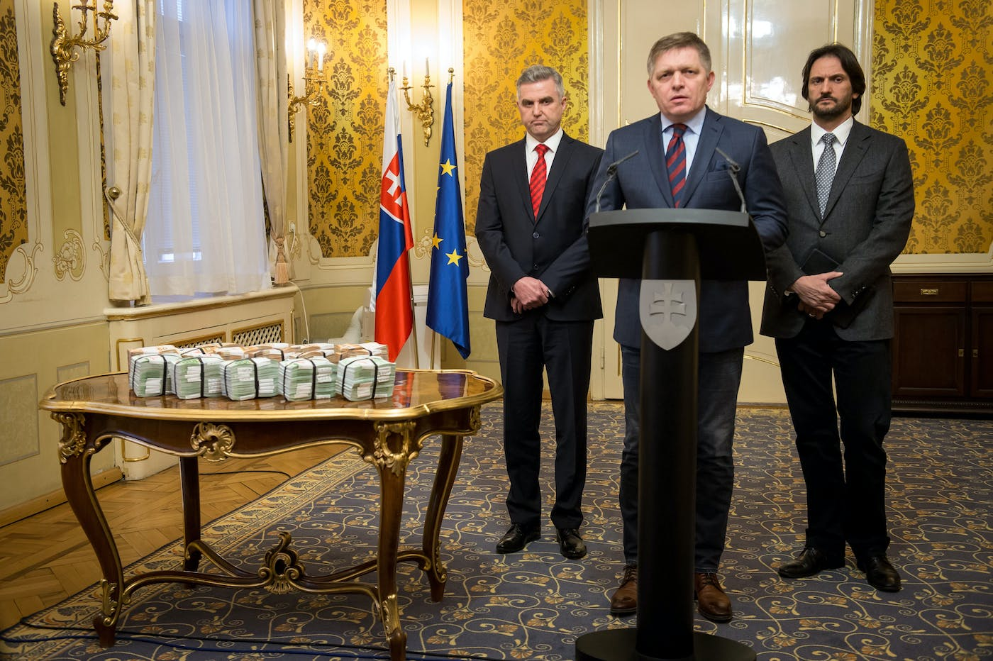 Slovak Prime Minister Robert Fico (C) is flanked by Slovak Police President Tibor Gaspar (L) and Slovak Interior Minister Robert Kalinak (R) as they stand next to bundles of Euro banknotes during a press conference on the murder case of a leading journalist who investigated high-profile tax fraud on February 27, 2018 in Bratislava, Slovakia.<br /><br /><br /> The body of Jan Kuciak, a 27-year-old reporter for the aktuality.sk news portal owned by Axel Springer and Ringier, was on Sunday (February 25, 2018) discovered alongside that of his fiancee Martina Kusnirova at their home in Velka Maca, 65 kilometres (40 miles) east of the Slovak capital Bratislava. Prime Minister Robert Fico said his government was offering one million euros ($1.2 million) for information leading to the killers' capture. / AFP PHOTO / VLADIMIR SIMICEK        (Photo credit should read VLADIMIR SIMICEK/AFP/Getty Images)