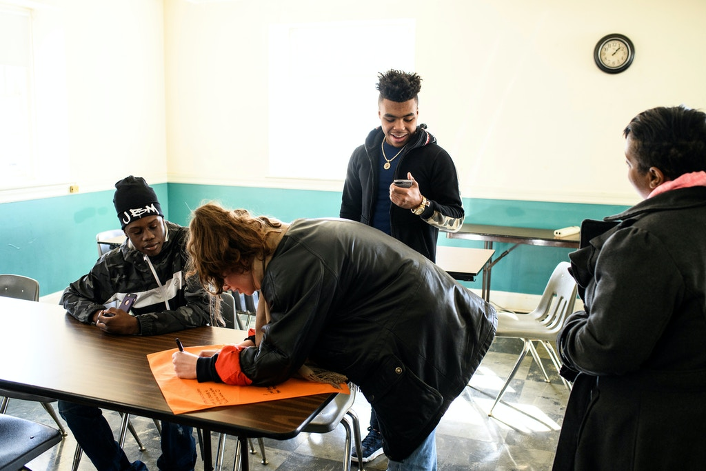 Baltimore, Maryland - February 03, 2018: (L-R) James Richardson, Mariah Guarnaccia, Keyonte Prince, and Sharon Jones sign a peace flag at a Ceasefire Art Installation at the Meeting House Stoney Run Meeting of Friends during the third Baltimore Ceasefire weekend, Saturday February 3rd, 2018.CREDIT: Matt Roth