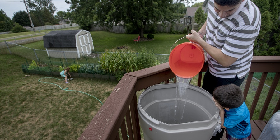 July 25, 2017 - Cottage Grove, MN, USA - Teddy Cuellar, 4, watched his father Matt pour water from the shower into a rain barrel on the deck of their Cottage Grove home. The family waters their garden from the barrel. ....   .. ] CARLOS GONZALEZ •  cgonzalez@startribune.com - July 25, 2017, Cottage Grove, MN, The long dry summer in Cottage Grove has lasted longer than the mayor predicted in May, when the City Council voted to shut down eight of the city's 11 wells and impose a strict watering ban on residents. The reason? Traces of decades-old 3M pollution were registering too high under new state Health Department guidelines. (Credit Image: © Carlos Gonzalez/Minneapolis Star Tribune via ZUMA Wire)