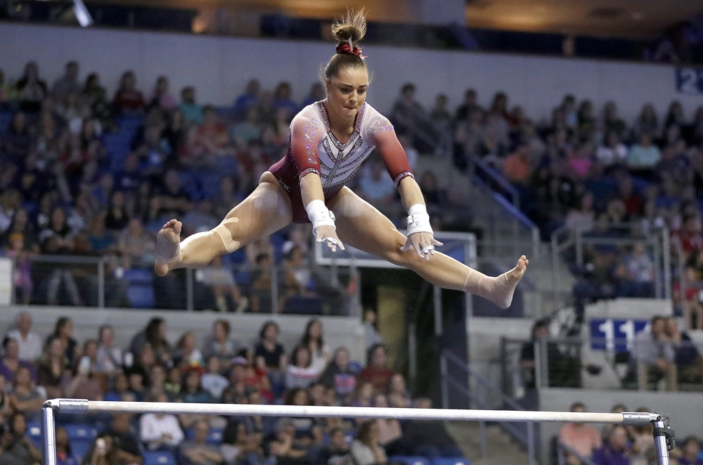 FILE- In this April 15, 2017, file photo, Oklahoma's Maggie Nichols competes on the uneven parallel bars during the NCAA college women's gymnastics championships in St. Louis. Nichols, a former Olympic hopeful, says she is among more than 100 women and girls who say they are victims of sexual abuse by a now-imprisoned Michigan sports doctor. She said in a statement Tuesday, Jan. 9, 2018, that Dr. Larry Nassar violated her innocence at the Karolyi Ranch Olympic training camp in Texas.  (AP Photo/Jeff Roberson, File)