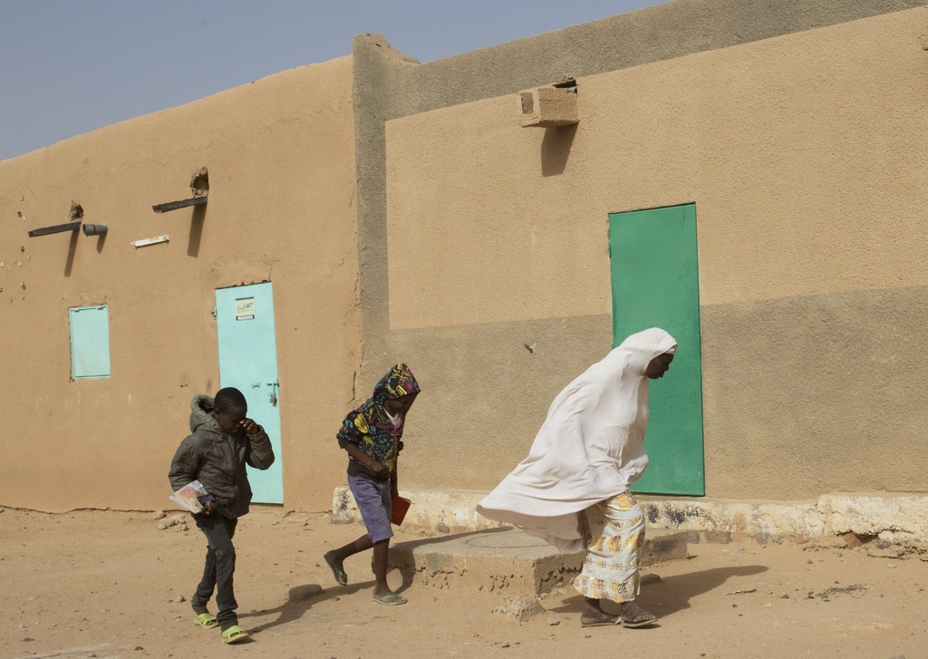 A woman and two children walk during blowing winds in Agadez, Niger, January 15, 2018.