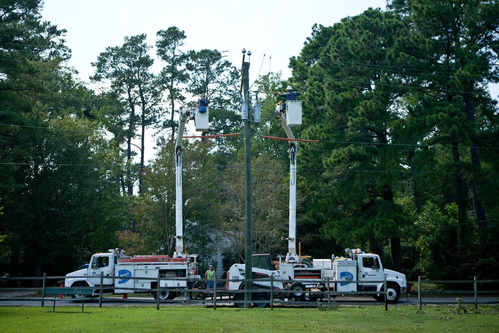 VIRGINIA BEACH, VA - AUGUST 28: Workers from Dominion Virginia Power tend to electrical lines affected by Hurricane Irene on August 28, 2011 in Virginia Beach, Virginia. The Category 1 storm, which made landfall in North Carolina early yesterday morning, has been downgraded to a tropical storm, but knocked out power to more than 3 million people and is attributed to 15 deaths as it travels up the Eastern seaboard. (Photo by Brendan Hoffman/Getty Images)