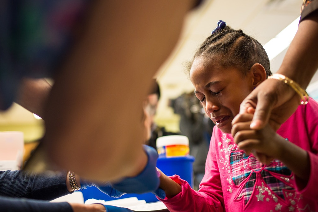 FLINT, MI - JANUARY 26:  Tears stream down the face of Morgan Walker, age 5 of Flint, as she gets her finger pricked for a lead screening on January 26, 2016 at Eisenhower Elementary School in Flint, Michigan.  Free lead screenings are performed for Flint children 6-years-old and younger, one of several events sponsored by Molina Healthcare following the city's water contamination and federal state of emergency.  (Photo by Brett Carlsen/Getty Images)