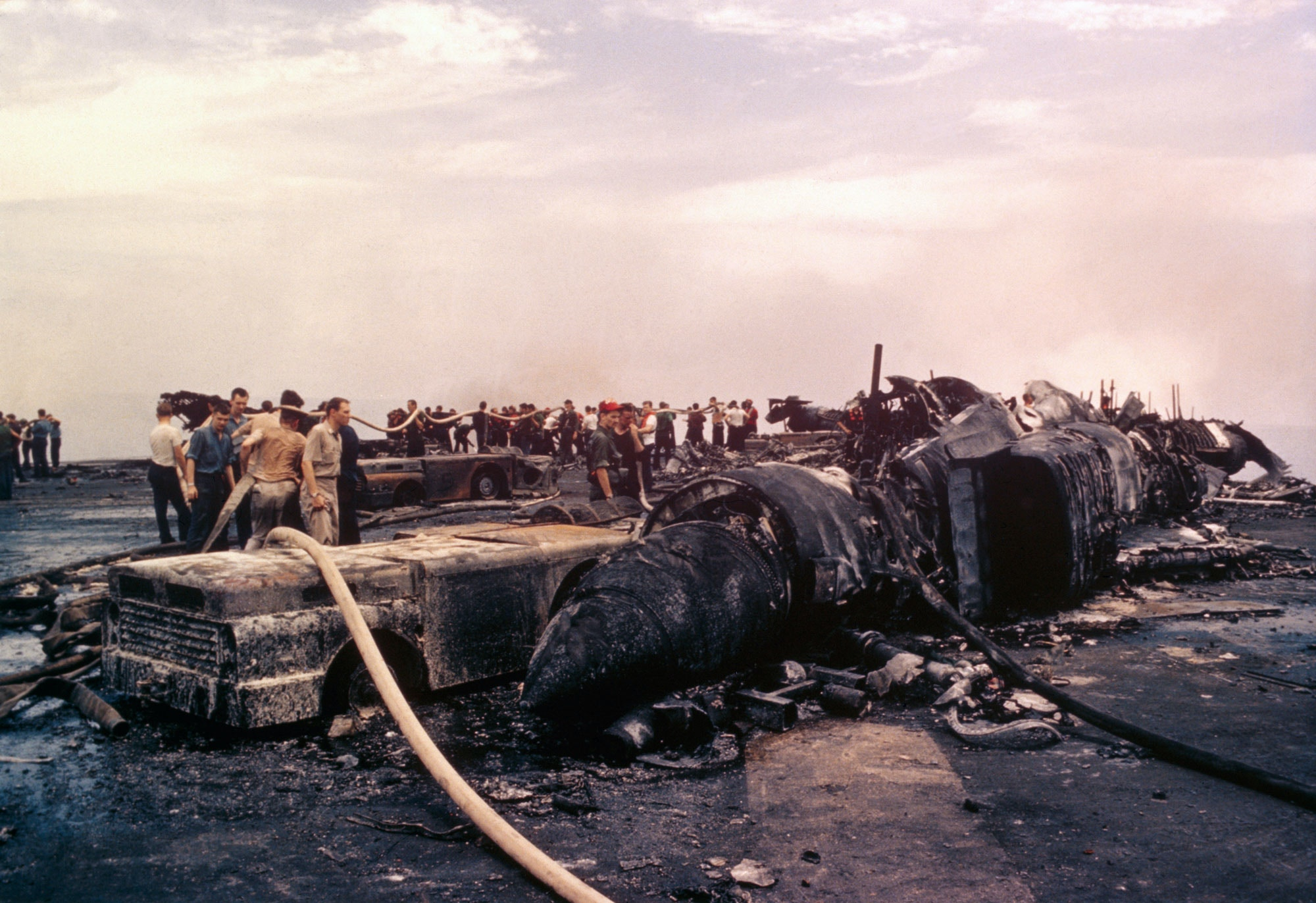 (Original Caption) Charred Wreckage on deck of USS Forrestal which suffered heavy damage when fire engulfing the ship exploded bombs and rockets of aircraft.