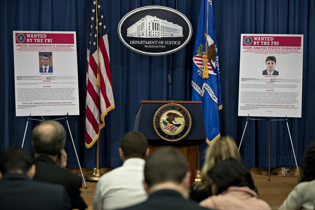 Wanted posters for Igor Anatolyevich Sushchin, right, and Dmitry Aleksandrovich Dokuchaev sit on display before a news conference at the Department of Justice in Washington, D.C., U.S., on Wednesday, March 15, 2017. The U.S. charged four people, including two Russian intelligence officers, over the theft of hundreds of millions of accounts of Yahoo Inc. users from a computer breach that threatened to derail its acquisition by Verizon Communications Inc. Photographer: Andrew Harrer/Bloomberg via Getty Images