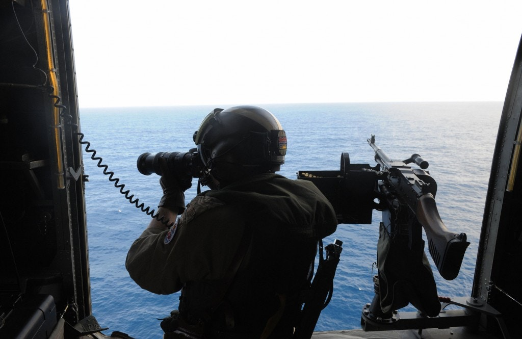 A Canadian Navy sailor on board a helicopter patrols the waters off the coast of Somalia as they escort a World Food Programme (WFP) ship on September 17, 2008, providing an anti-pirate escort for the ship taking food aid to Somalia. The UN Security Council in June adopted a resolution authorising foreign warships to enter Somalia's territorial waters with the government's consent to combat pirates, though it has yet to be implemented. European foreign ministers agreed to set up a special unit to coordinate the fight against piracy off Somalia, raising the possibility of a EU naval mission to the region. Ninety percent of food aid is delivered to the Horn of Africa country by ship, the last lifeline for starving millions since insurgents armed with surface-to-air missiles make air and road deliveries too dangerous. AFP PHOTO/SIMON MAINA (Photo credit should read SIMON MAINA/AFP/Getty Images)