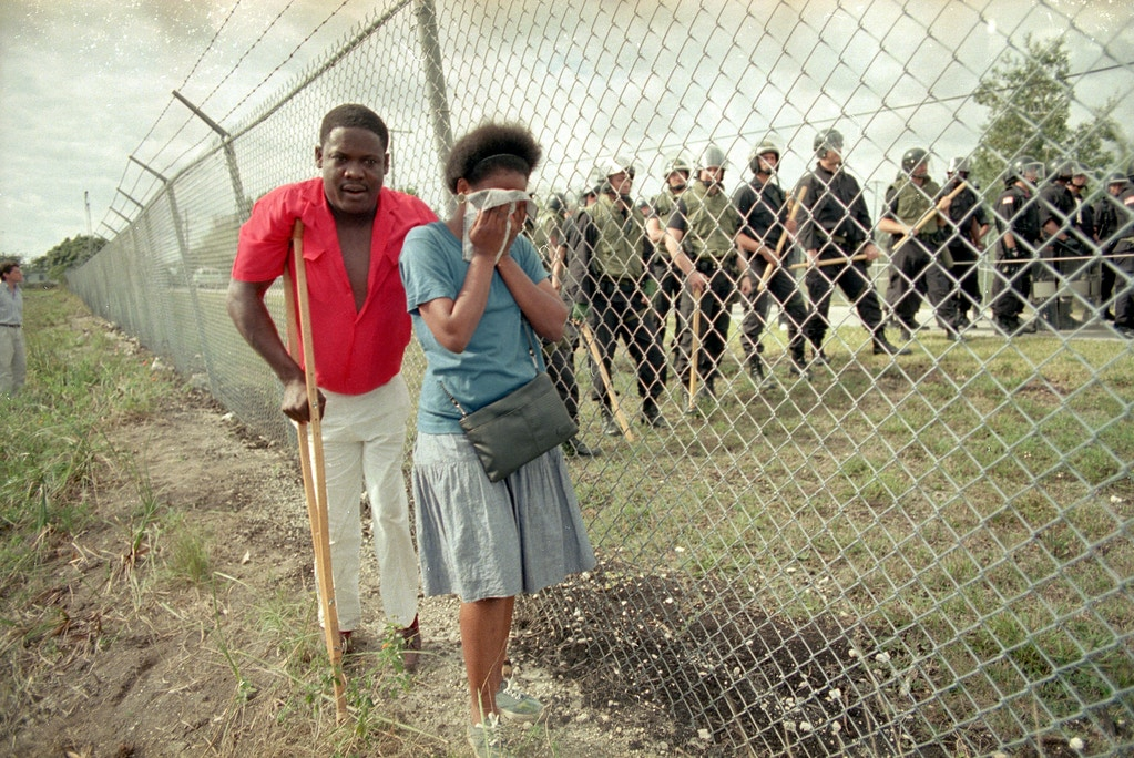 Paula Vivaldy cries as she and friend Bilatois Thermidor walk beside the barbed wire fence at the U.S. Immigration Service's Krome Avenue Detention Center where some 200 Haitians gathered to protest the treatment of Haitians held there, Jan. 29, 1989.  Inside the fence several dozen federal officers in riot gear stand at the ready for any trouble. (AP Photo/Kathy Willens)